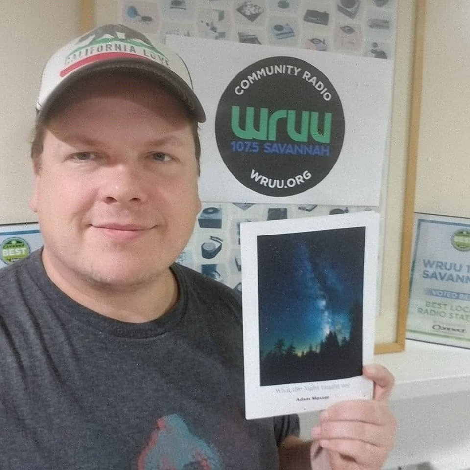 Adam Messer holding up his poetry book What the night taught me. Background is at the WRUU 107.5 FM Savannah studio.